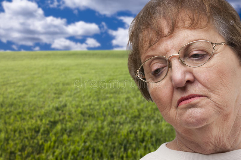 Download Melancholy Senior Woman With Grass Field Behind Stock Photo - Image: 36770028