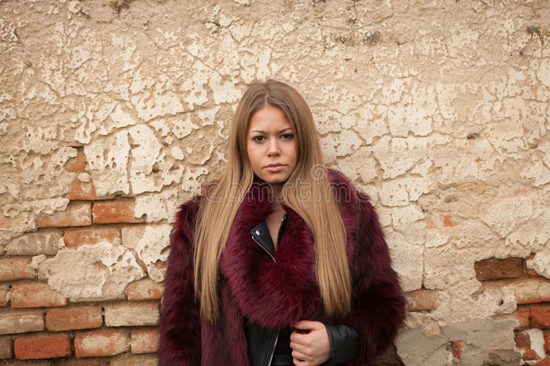 Melancholy young girl with red fur coat. Looking at camera stock photos