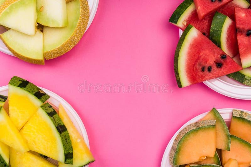 Melancia e fatias de melão na placa, visão superior sobre fundo de pastel rosa, bandeja plana fotografia de stock royalty free