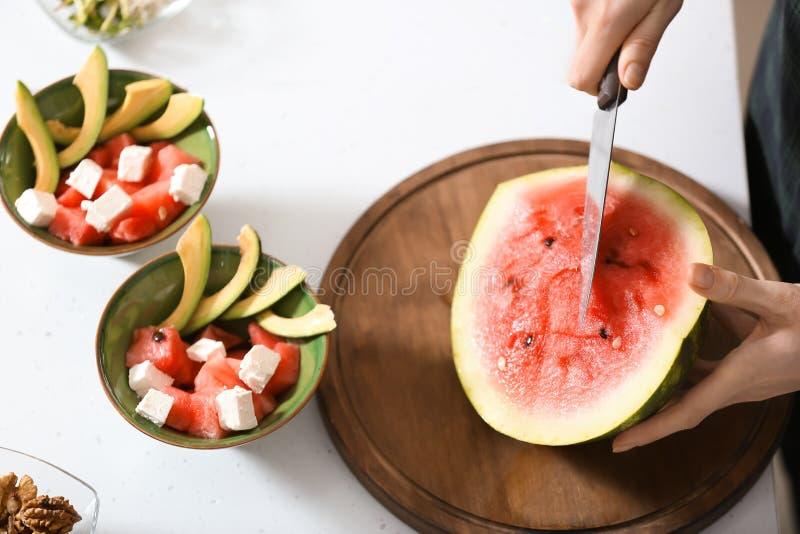 Melancia madura do corte da mulher para a salada na cozinha imagens de stock royalty free