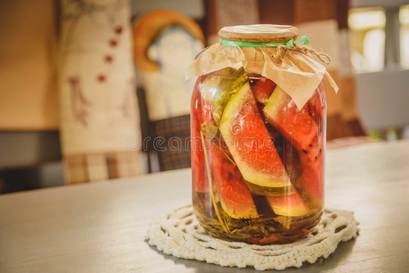 Melancia posta de conserva ou conservada com ervas em um frasco de vidro em uma tabela de madeira em uma cozinha imagem de stock royalty free