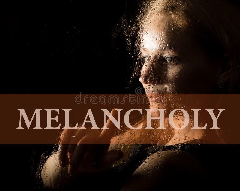 Melancolia escrita na tela virtual Mão da melancolia da jovem mulher e triste na janela na chuva imagens de stock