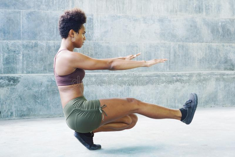 Melanesian pacific islander athlete girl with afro performing exercising routines sitting plank royalty free stock photos