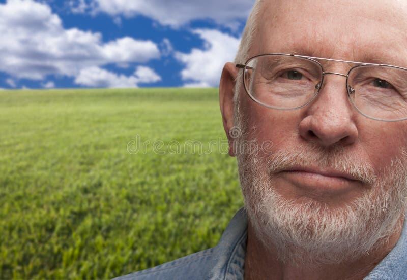 Melankolisk hög man med gräsfältet bakom arkivfoton
