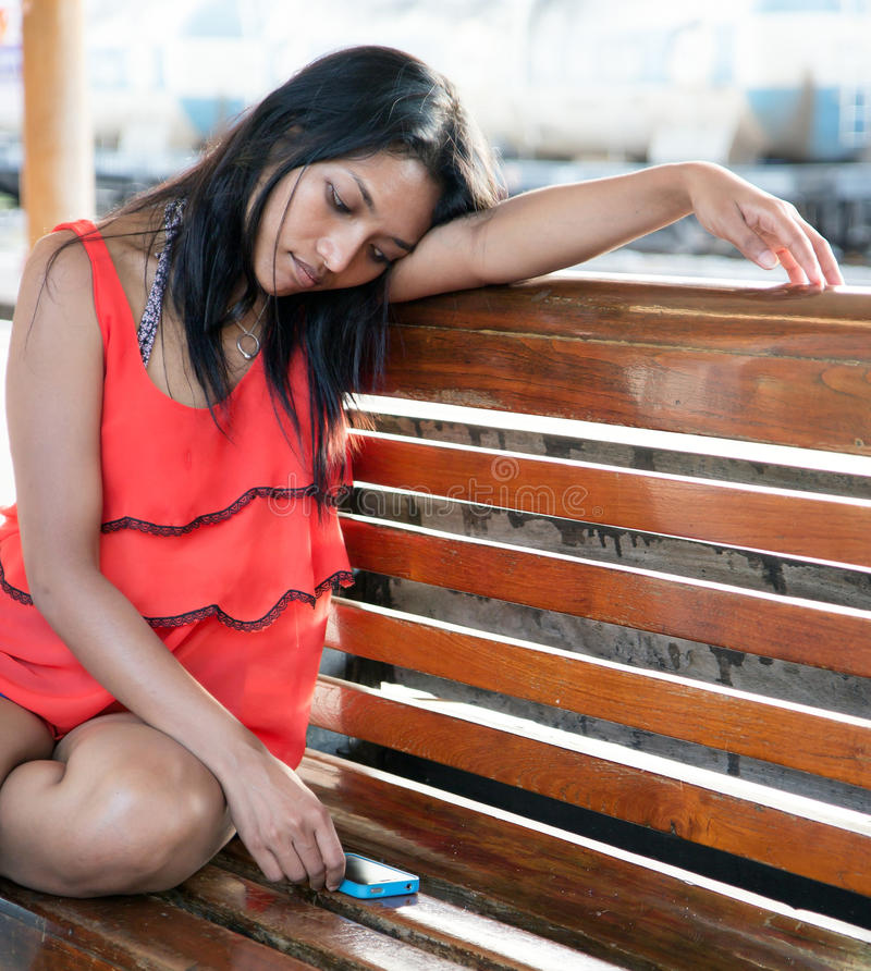 Melankoliskt flickasammanträde på en bänk royaltyfria foton