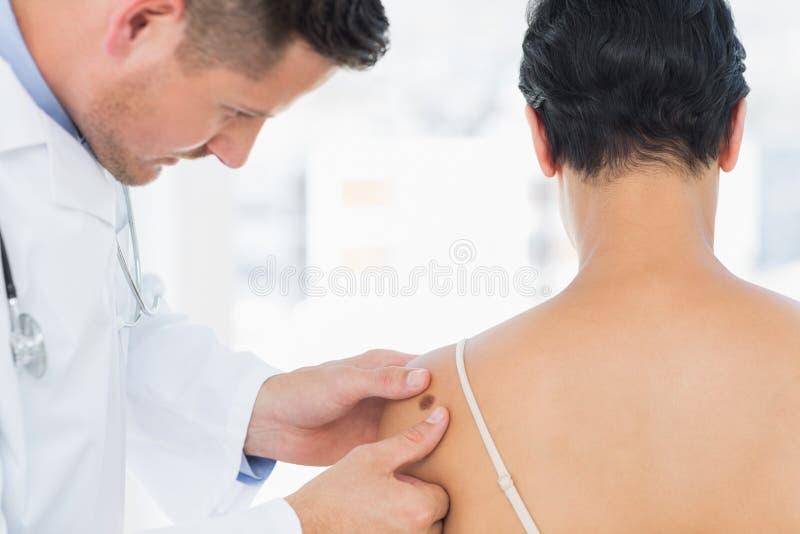 Melanoma de exame do doutor na mulher imagem de stock