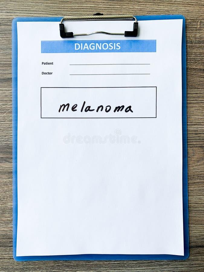 Melanoma do diagnóstico em um formulário médico na mesa do doutor fotos de stock