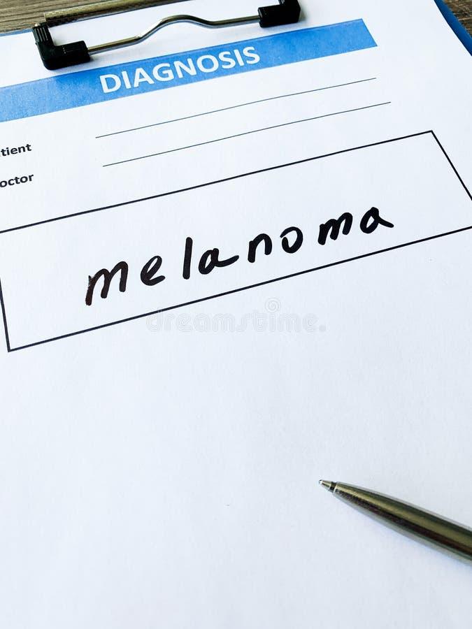 Melanoma do diagnóstico em um formulário médico na mesa do doutor fotografia de stock royalty free