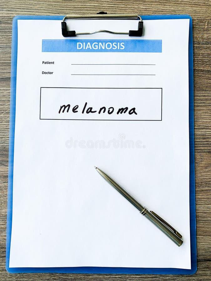 Melanoma do diagnóstico em um formulário médico na mesa do doutor fotos de stock royalty free