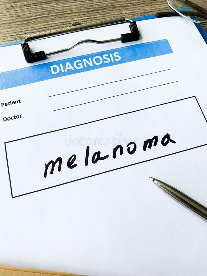 Melanoma do diagnóstico em um formulário médico na mesa do doutor imagem de stock