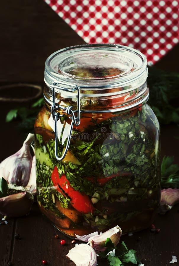 Melanzana arrostita inscatolata casalinga e peperone dolce con aglio, prezzemolo, aceto ed olio in barattolo di vetro, natura mor fotografia stock
