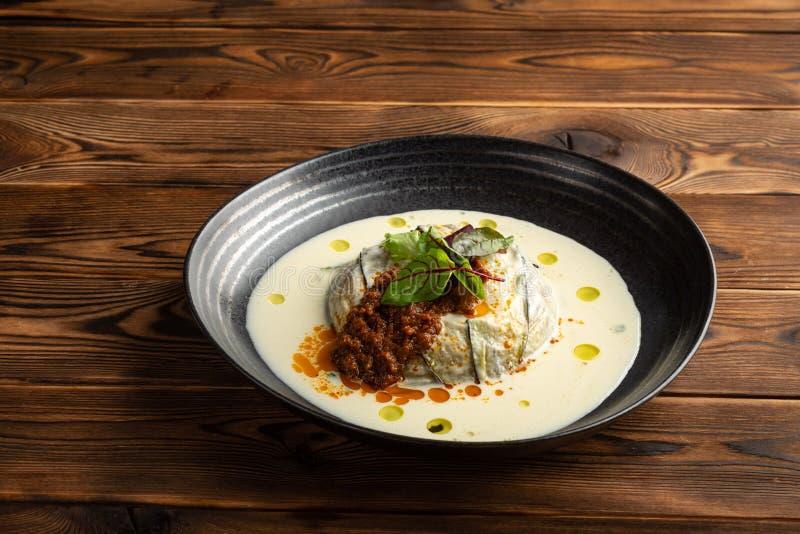 Melanzana calda con il latte del parmigiano e degli spinaci in un piatto su un fondo di legno immagini stock