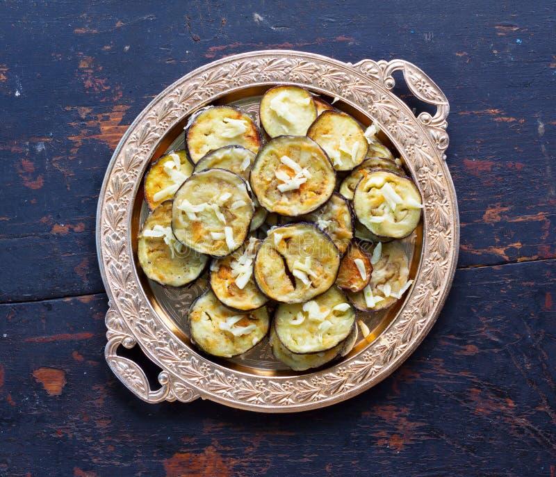 Melanzana fritta con aglio in un piatto dorato sulla vecchia tavola di legno blu scuro immagine stock libera da diritti