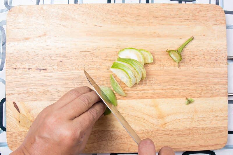 Melanzana tailandese del taglio manuale su vasto di legno immagine stock