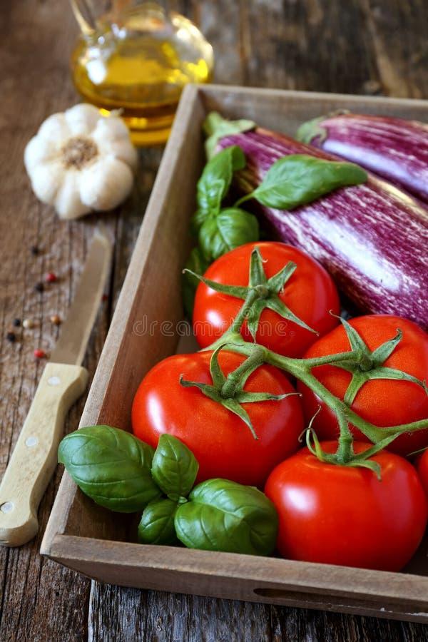 Melanzane dei graffiti, pomodori in vassoio, aglio e olio d'oliva immagine stock libera da diritti