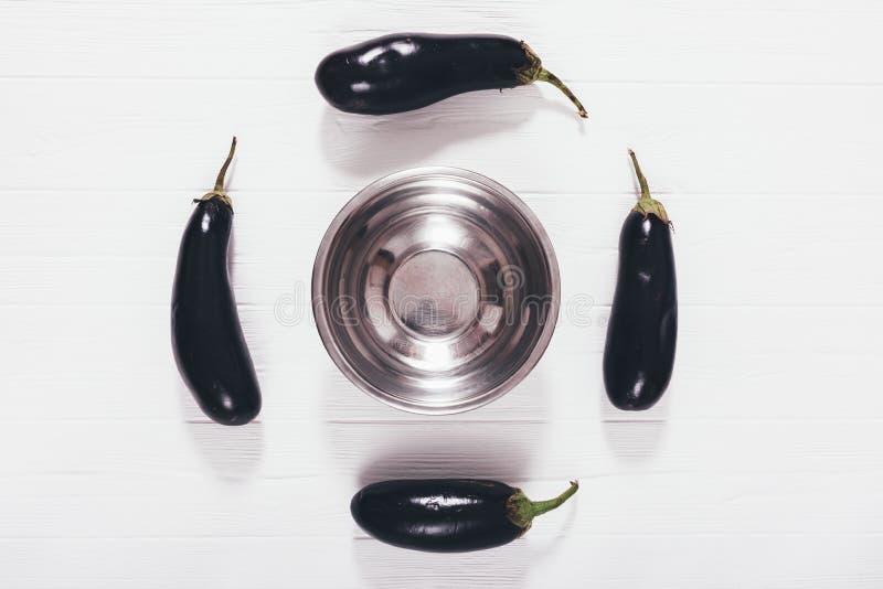Melanzane della composizione degli alimenti e ciotola porpora del metallo fotografia stock