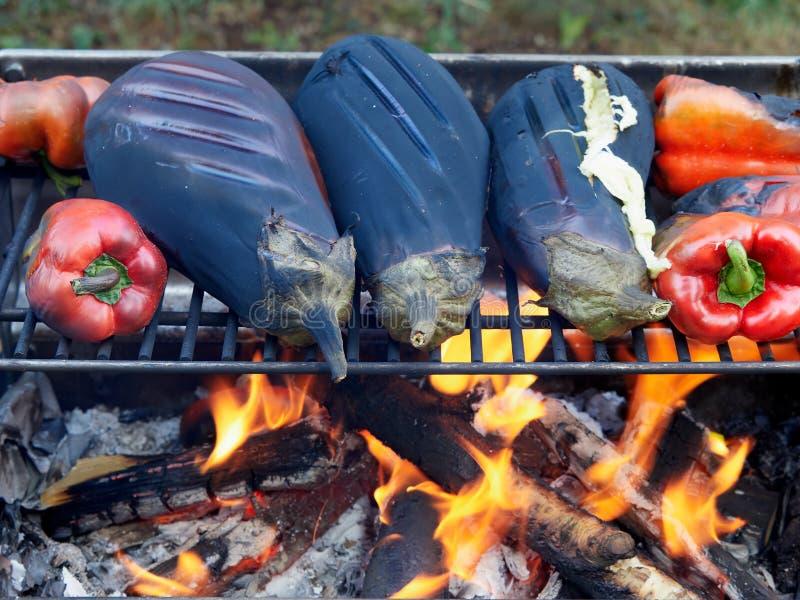 Melanzane e peperoni che cuociono sull'arrosto all'aperto fotografia stock