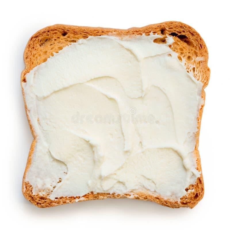 Melba rostat bröd med gräddost som isoleras på vit från över arkivfoto