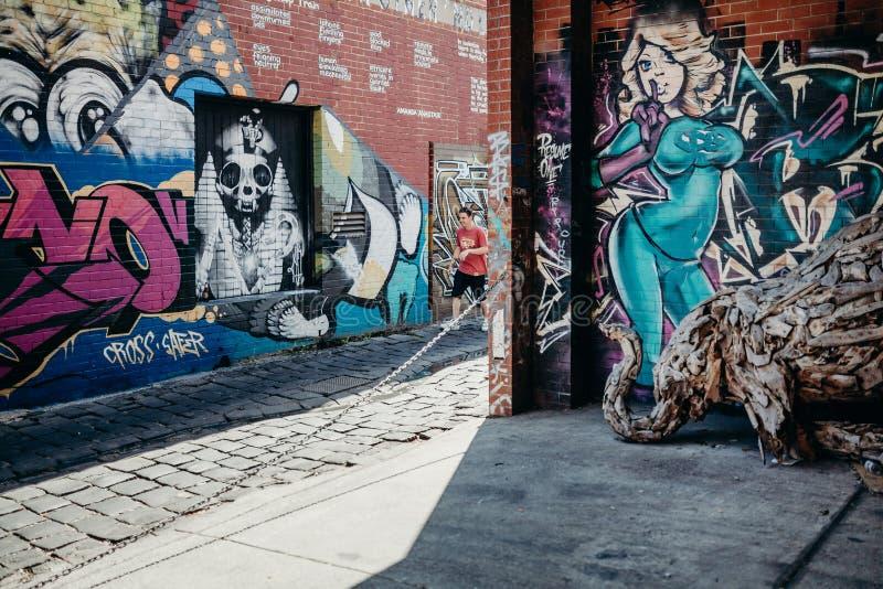 MELBOURNE, AUSTRÁLIA - 12 de março de 2017: Povos que andam ao longo das paredes de observação dos grafittis da rua em Melbourne, fotos de stock
