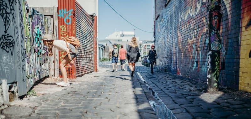 MELBOURNE, AUSTRÁLIA - 12 de março de 2017: Povos que andam ao longo das paredes de observação dos grafittis da rua em Melbourne, imagem de stock royalty free