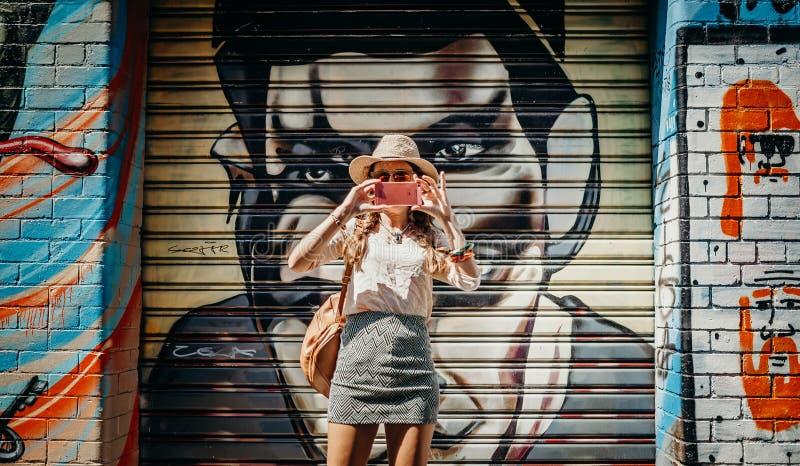 MELBOURNE, AUSTRÁLIA - 12 de março de 2017: Turista que toma uma foto da parede dos grafittis, com um grafitti no fundo, em Melbo fotografia de stock