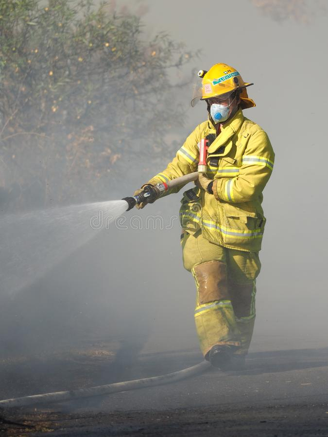 Fire fighter spraying water on a bush fire in an suburban area of Knox City in Melbourne east. Melbourne, Australia - April 13, 2018: Fire fighter spraying stock photos