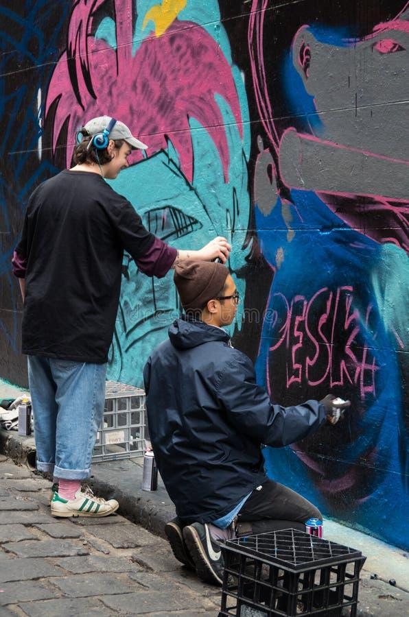 Melbourne street artists in Hosier Lane, a venue for legal street art. Melbourne, Australia - August 8, 2015: street artists working on artworks in Hosier Lane stock image