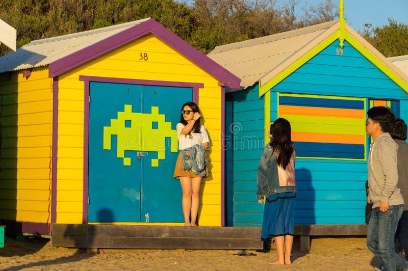 Melbourne, Australia - 31 de marzo de 2018: Turistas que presentan delante de las cajas de baño coloridas en Brighton Beach, un c imagenes de archivo