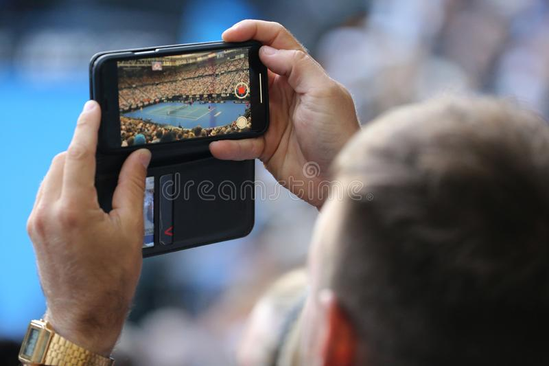 Unidentified spectator uses his cell phone to take images during tennis match at 2019 Australian Open in Melbourne Park. MELBOURNE, AUSTRALIA - JANUARY 27, 2019 royalty free stock images