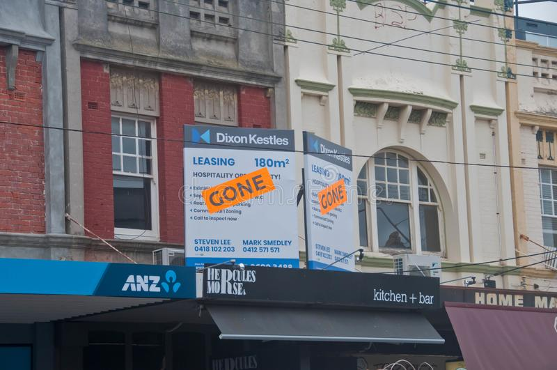MELBOURNE, AUSTRALIA - JULY 30, 2018: Gone banner pasted on top of lease ads of office space above ANZ bank in South area of stock photo