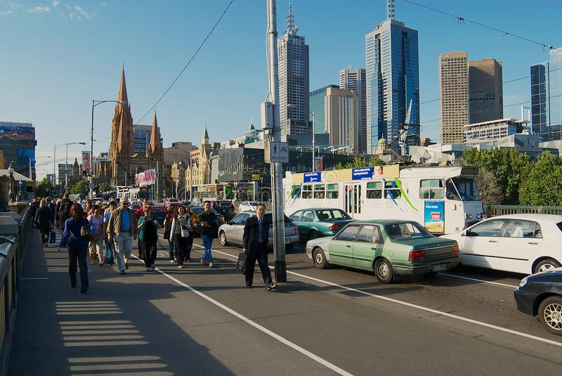 People walk by the street with the city center buildings at the background in Melbourne, Australia. MELBOURNE, AUSTRALIA - NOVEMBER 14, 2007: Unidentified royalty free stock image