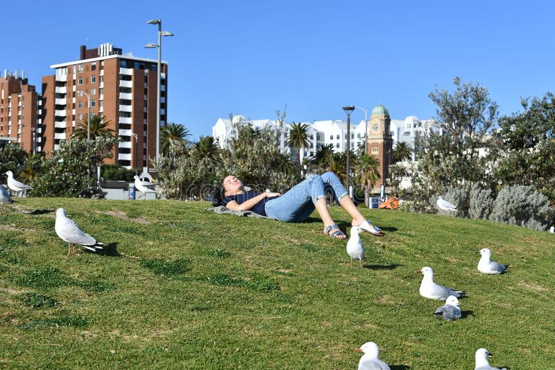 MELBOURNE, AUSTRALIEN - 14. August 2017 - Leute, die auf St. Kilda den Strand sich entspannen stockbilder