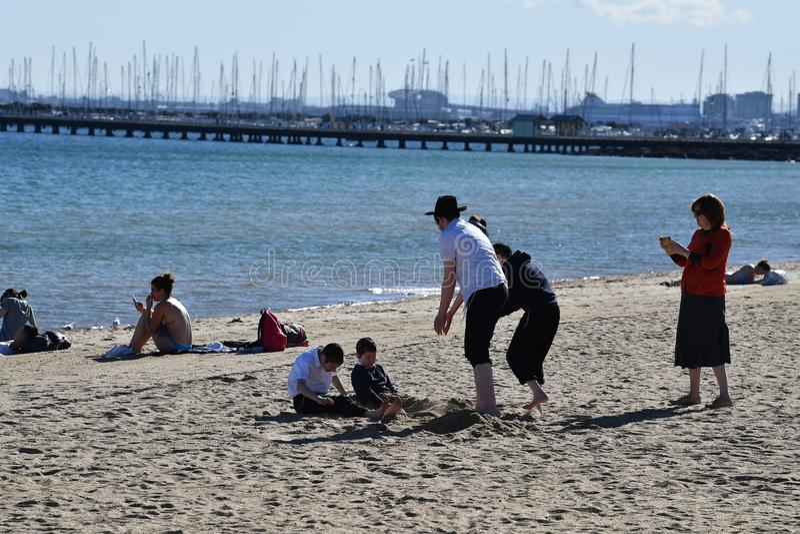 MELBOURNE AUSTRALIEN - AUGUSTI 14, 2017 - folk som kopplar av på st Kilda stranden arkivfoto