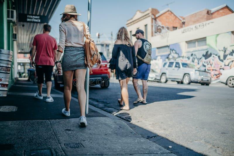 MELBOURNE AUSTRALIEN - mars 12, 2017: Folk som promenerar de hållande ögonen på grafittiväggarna för gata i Melbourne, Australien arkivfoto