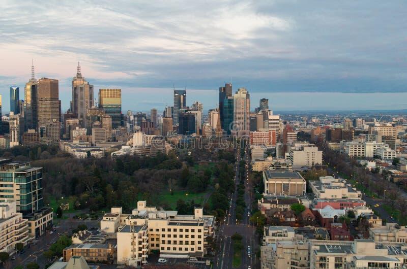 Melbourne CBD på soluppgång med Fitzroy trädgårdar royaltyfri foto