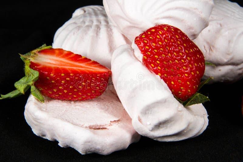 Melcochas blancas, fresas rojas, fondo negro fotos de archivo