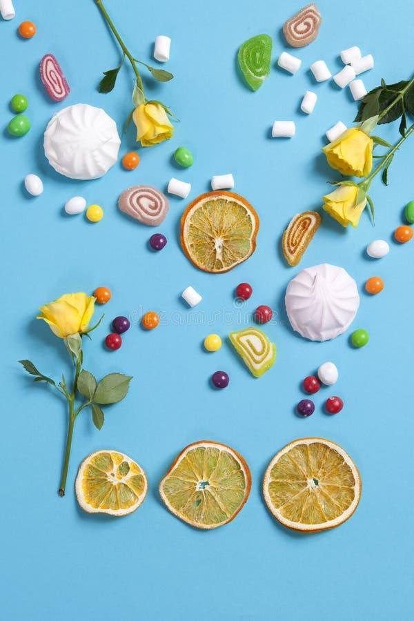 Melcochas, caramelo, habas de jalea, dulces y naranjas secas de las tazas cayendo en cono de la oblea en fondo azul imagen de archivo