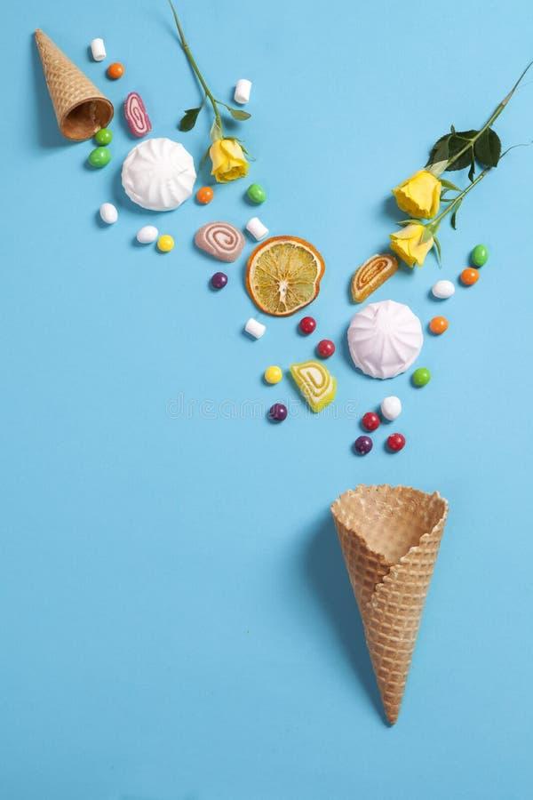 Melcochas, caramelo, habas de jalea, dulces y naranjas secas de las tazas cayendo en cono de la oblea en fondo azul imagenes de archivo