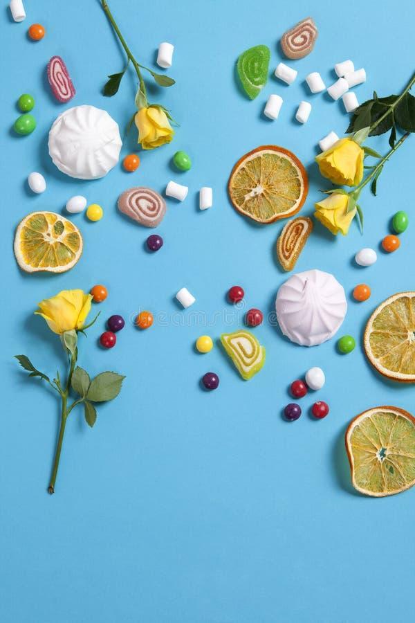 Melcochas, caramelo, habas de jalea, dulces y naranjas secas de las tazas cayendo en cono de la oblea en fondo azul foto de archivo libre de regalías