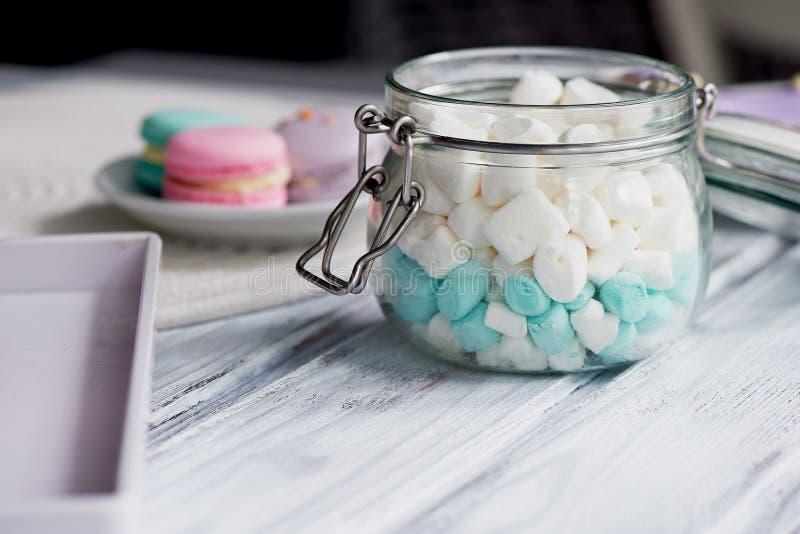 Melcochas en los colores en colores pastel blancos y azules en una superficie de madera ligera En un tarro de cristal con una tap fotos de archivo
