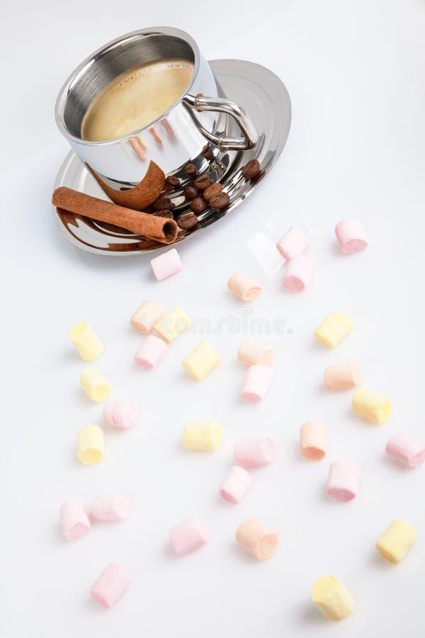 Melcochas multicoloras en un fondo blanco Detrás de ellos es una taza de café con los granos y el canela imagen de archivo libre de regalías