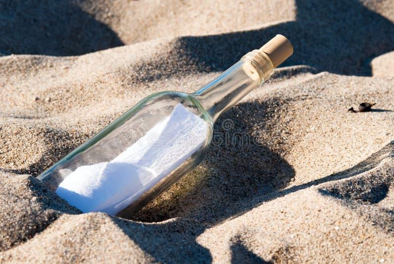 Meldung in einer Flasche im Sand lizenzfreie stockbilder