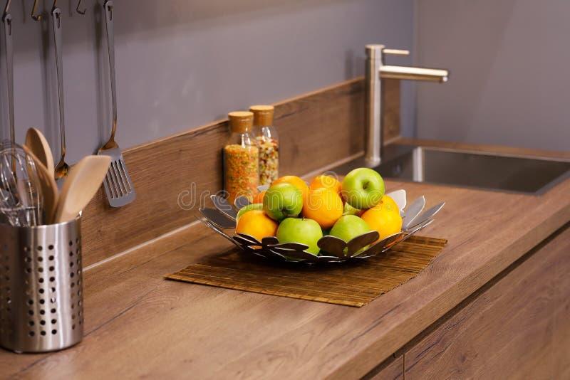 Mele e arance sul bancone della cucina in legno immagini stock libere da diritti