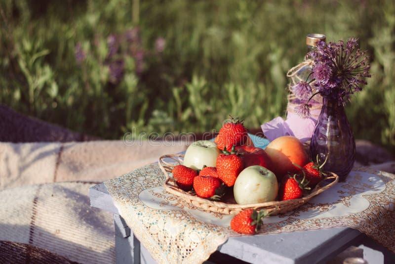 Mele e fragole su un piatto di vimini, fiori porpora in un vaso di vetro, su un panchetto di legno con un tovagliolo decorativo fotografia stock