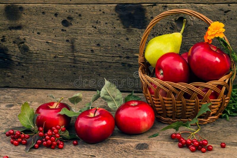Mele e pera rosse in un canestro su un fondo di legno fotografia stock libera da diritti