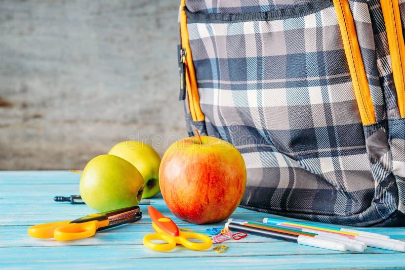 Mele e zaino della scuola su fondo di legno fotografia stock libera da diritti