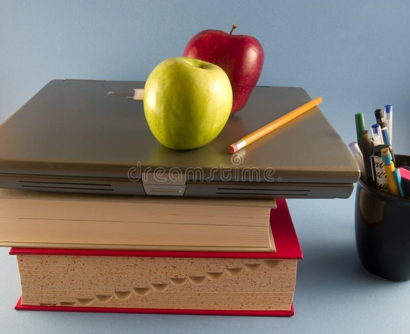 Mele, libri e computer portatile immagine stock