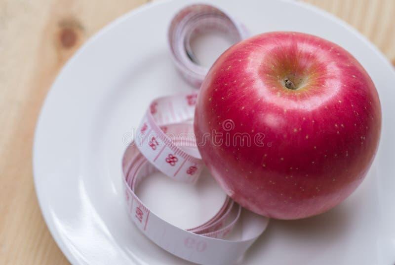 Mele rosse delizia e misurato il metro su fondo di legno, alimento sano, concetto di dieta immagini stock