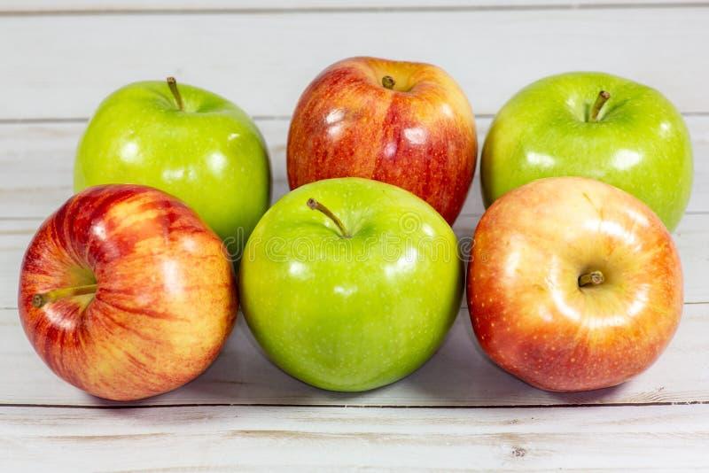 Mele rosse e verdi che aspettano per essere mangiato sul tavolo da cucina fotografia stock