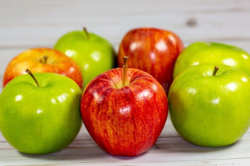 Mele rosse e verdi che aspettano per essere mangiato sul tavolo da cucina immagini stock